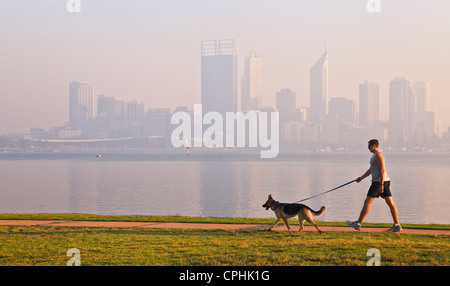 Man walking a dog down path beside river with the silhouette of a misty city skyline in the background. - Stock Photo