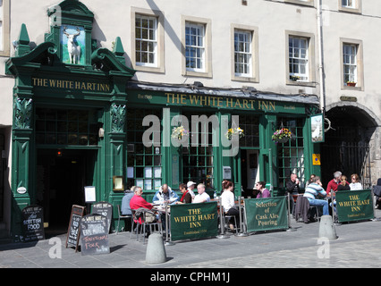 People sitting drinking outside the White Hart Inn within  Grassmarket, Edinburgh Scotland UK - Stock Photo