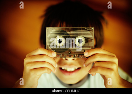 Boy holds old casette tape. - Stock Photo