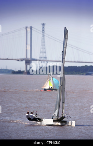A catamaran at a regatta on the River Severn estuary with the first Severn Bridge nearest and second Severn crossing - Stock Photo