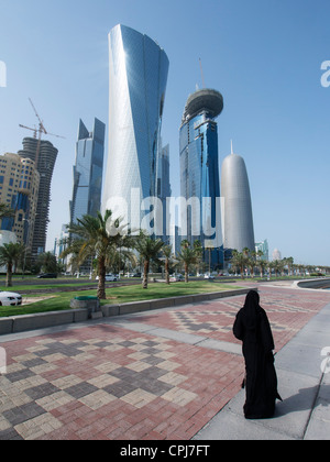 Woman in abaya walking in front of modern skyscrapers in new business district of Doha in Qatar - Stock Photo