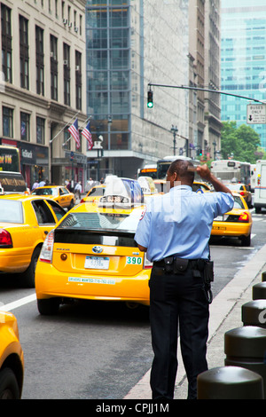 New York City police officer combing his hair as iconic yellow taxis pass by - Stock Photo