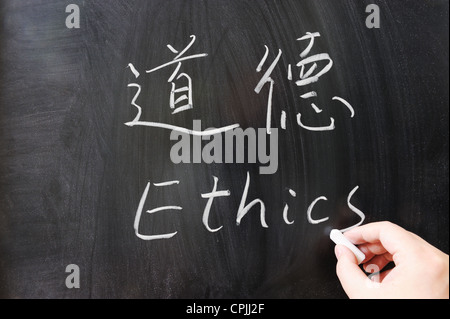 Ethics word in Chinese and English written on the chalkboard - Stock Photo