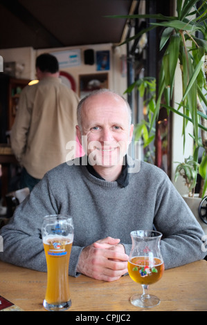 40 something man sat at table in bar with two glasses of beer - Stock Photo
