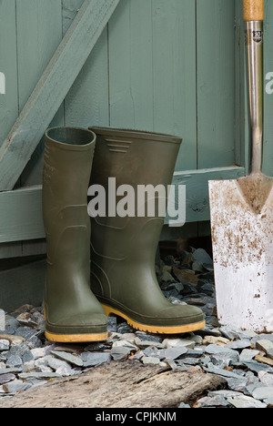 Pair of green wellington boots and a spade outside a garden shed. - Stock Photo
