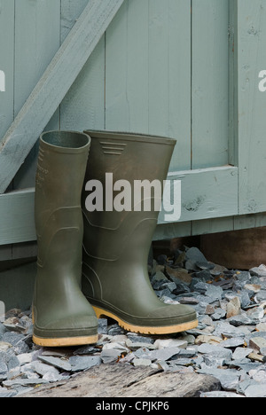Pair of green wellington boots outside a garden shed. - Stock Photo