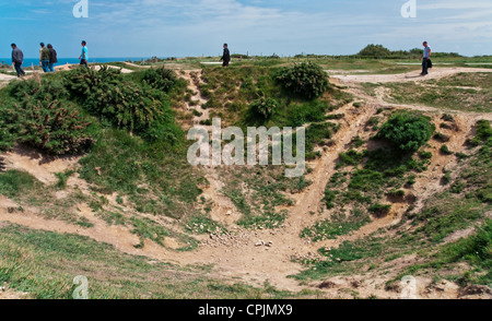 Point du hoc, Normandy, France. People walk by a bomb crater from the 1944 Normandy invasion, 'Operation Overlord'. - Stock Photo