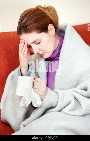 A young sick woman with a cup of tea in her hand. She hold her head in pain - Stock Photo