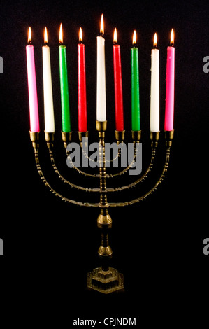 Candles on a menorah for the Jewish holiday Hanukkah that is observed for eight nights and days. - Stock Photo