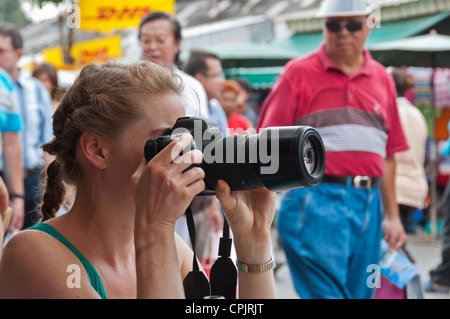 Caucasian Female Photographer taking pictures from visitors of Chatuchak Market Jatujak Bangkok Thailand Southeast - Stock Photo