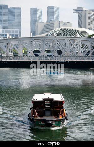 A tourist boat passes beneath the Anderson Bridge with the Esplanade area in the background. - Stock Photo