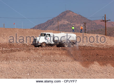 Water truck spraying water on road under construction operator visible in cab two people standing on bank Arizona - Stock Photo