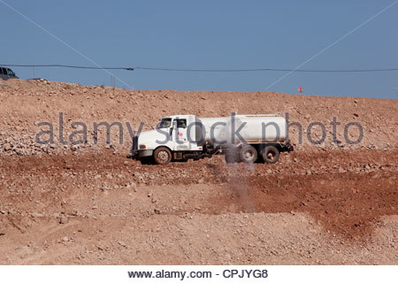 Water truck spraying water on road under construction operator visible in cab Arizona - Stock Photo
