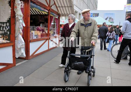Berlin, Germany. Man with walking aid / shopping trolley in Alexanderplatz - Stock Photo
