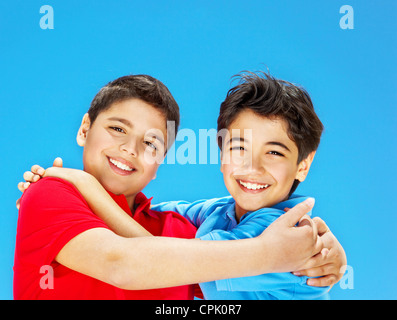 Cute boys smiling over blue sky, preteens playing outdoor, kids holding hands, best friends hug, beautiful children - Stock Photo