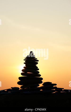 Stacked pebbles silhouette against a sunset. UK - Stock Photo