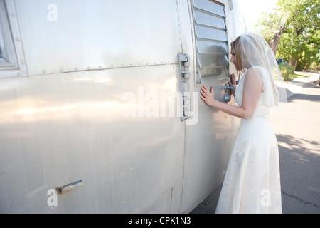 Bride peeking into the window of an Airstream trailer. - Stock Photo