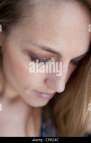 Close up of a woman looking down with serious expression. - Stock Photo
