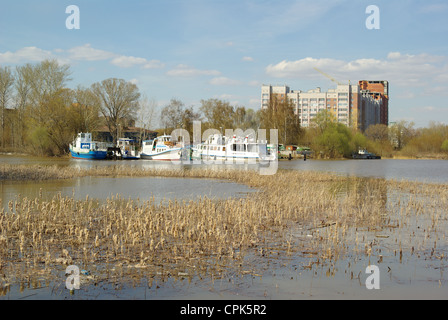 Multistoried buildings on the sky background, white ship and reed foreground in Kazan, Tatarstan, Russia - Stock Photo