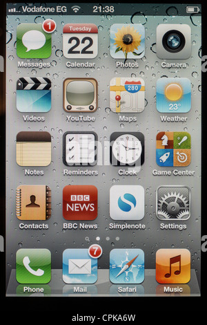 screen of Apple iPhone 4s showing applications on home page with new emails and new message - Stock Photo
