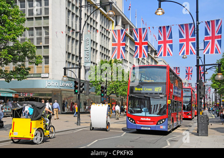 London rickshaws and red buses outside John Lewis store in Oxford Street with Jubilee Union Jacks which may also - Stock Photo