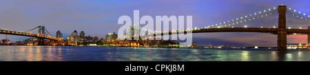 ultrawide angle of the Brooklyn Bridge and Manhattan Bridge spanning the East River towards Brooklyn in New York - Stock Photo
