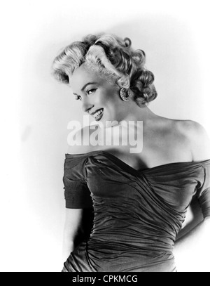 A color portrait of the film star Marilyn Monroe, pictured in 1957. She is smiling at the camera in this half body - Stock Photo