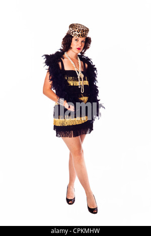 A brunette woman poses as a 1920's flapper in a lampshade dress. Image shot in studio over a white background - Stock Photo