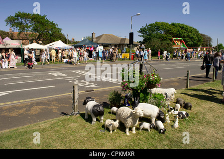 Sculptures of sheep and farmyard animals set on grass under a 4-arm hanging basket roadside at Yarmouth Old Gaffers - Stock Photo