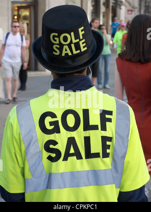 A person standing wearing an advert for a golf sale - Stock Photo