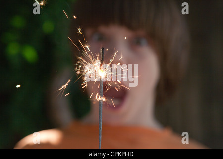 Close up of a boy holding a sparkler with surprised expression on his face. - Stock Photo