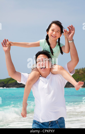 asian father with little girl running on the beach - Stock Photo