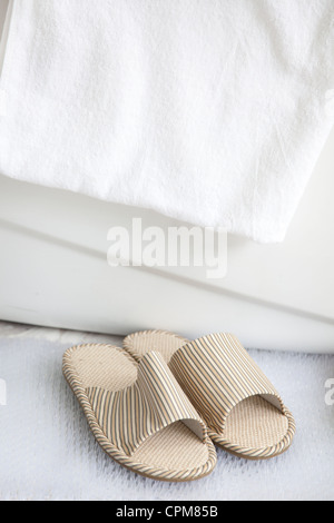 Slippers on bath mat by the bathtub with towel - Stock Photo