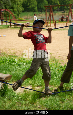 children training and walking on rope - slacline with mother summer park - Stock Photo