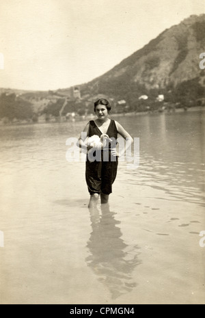 Woman Bather in a Lake Holding Pet Duck - Stock Photo