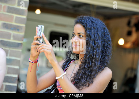 A young woman using her camera phone to take a picture. - Stock Photo