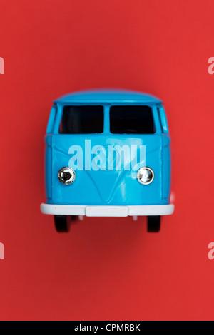 Blue Matchbox Die cast Volkswagen van on red background - Stock Photo