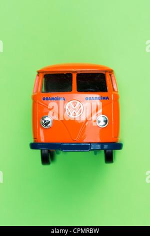 Orange Matchbox Die cast Volkswagen van on green background - Stock Photo