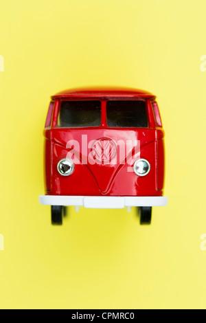 Red Matchbox Die cast Volkswagen van on yellow background - Stock Photo