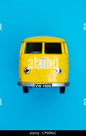 Yellow Matchbox Die cast Volkswagen van on blue background - Stock Photo