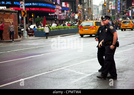 NYPD police officers in Times Square, New York city, Manhattan patrolling the streets looking for trouble - Stock Photo
