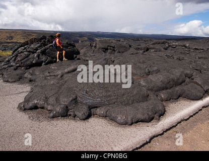 Elk284-2635 Hawaii, HI, Volcanoes NP, South Coast recent lava flow on road, with hiker, Model released - Stock Photo