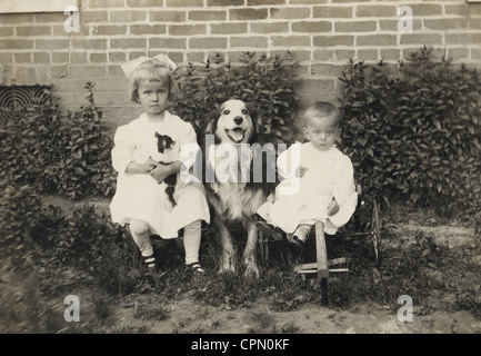 Two Little Children with Large Dog Between Them - Stock Photo
