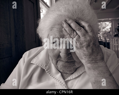 Apprehensive worried vulnerable senior elderly old age lady in large living room - Stock Photo