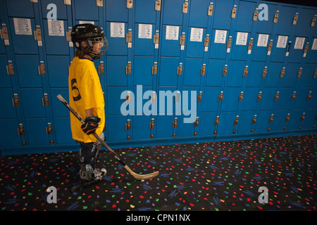 Nine year old boy dressed for roller hockey standing in front of a wall of blue lockers. - Stock Photo