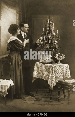 Christmas, couple celebrating Christmas, Christmas presents and small fir tree on the table, Germany, 1919, Additional - Stock Photo