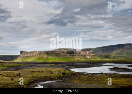 Iceland, stream running through lava field, basalt cliffs in the distance - Stock Photo