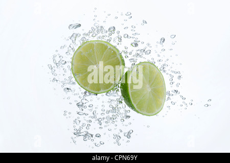 Lime halves submerged in sparkling water - Stock Photo