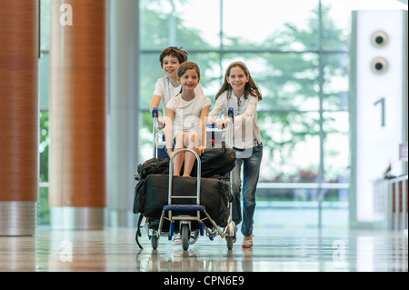Brother and sister pushing younger sister on luggage cart in airport - Stock Photo