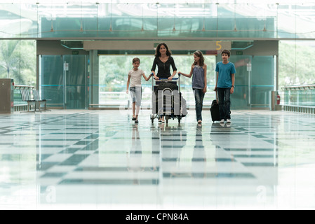 Family pushing luggage cart in airport lobby - Stock Photo